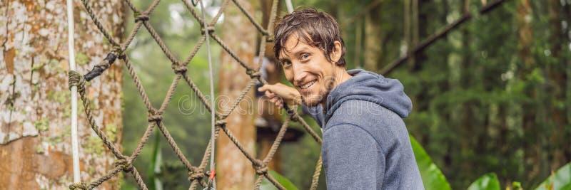 Сильные молодые люди в парке веревочки на деревянном ЗНАМЕНИ предпосылки, ДЛИННОМ ФОРМАТЕ стоковое изображение rf