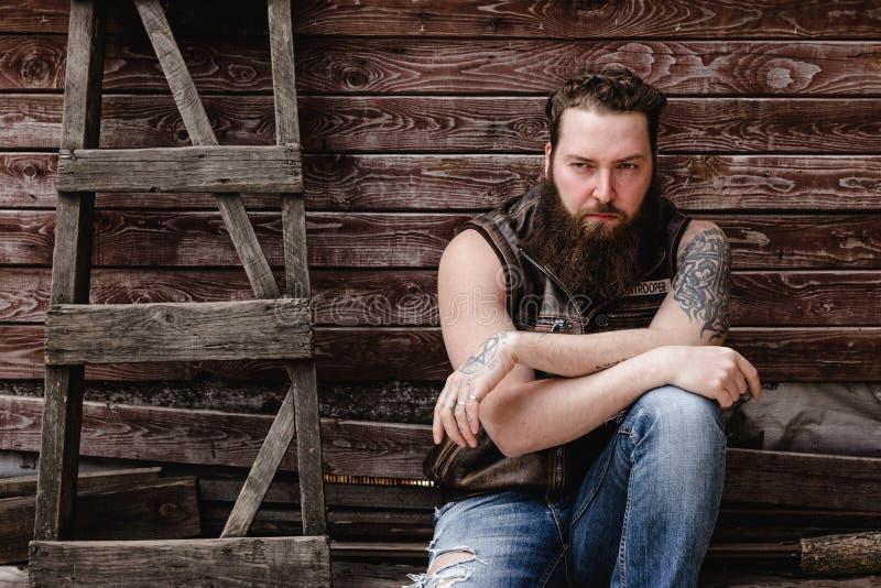 Сильный зверский человек с бородой и татуировками на его руках одетых в кожаных жилете и джинсах сидит на деревянной стене стоковое изображение rf