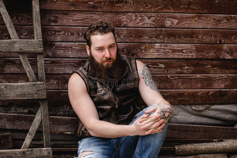 Сильный зверский человек с бородой и татуировками на его руках одетых в кожаных жилете и джинсах сидит на деревянной стене стоковые фотографии rf