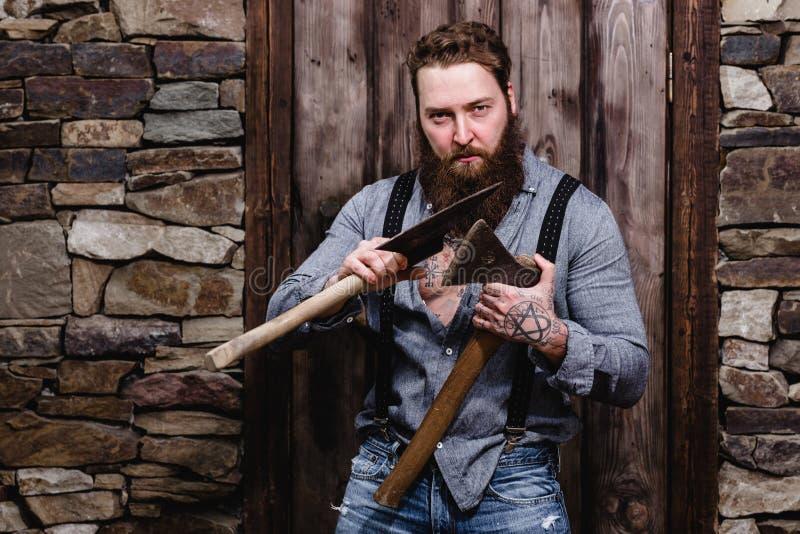 Сильный зверский человек с бородой и татуировки на его руках одетых в стильных стойках случайных одежд с 2 осями в его стоковое фото