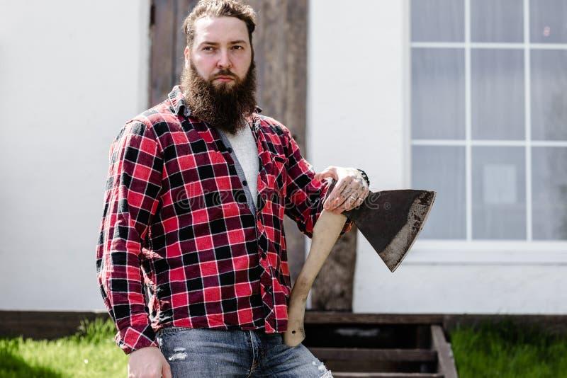 Сильный зверский человек с бородой одетой в проверенной рубашке стоя с осью в руке на фоне стоковые изображения rf