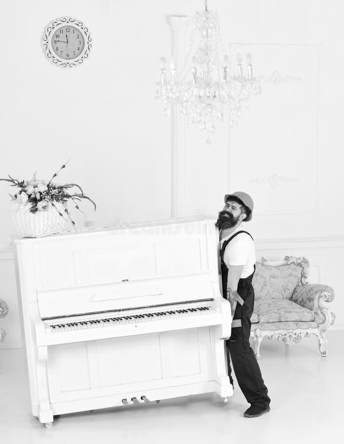 Сильный человек поднимая тяжелую старую деревянную вазу рояля и стекла при цветки изолированные на белой предпосылке Работник про стоковые фотографии rf