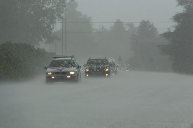 Сильный шторм с проливным дождем на дороге с плохой видимостью автомобилей Концепция опасности управлять в плохой погоде стоковое фото rf