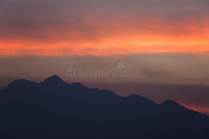 Сильуэтическое закатное небо с горами красивые оранжевые облака после захода солнца на задний план стоковое изображение rf
