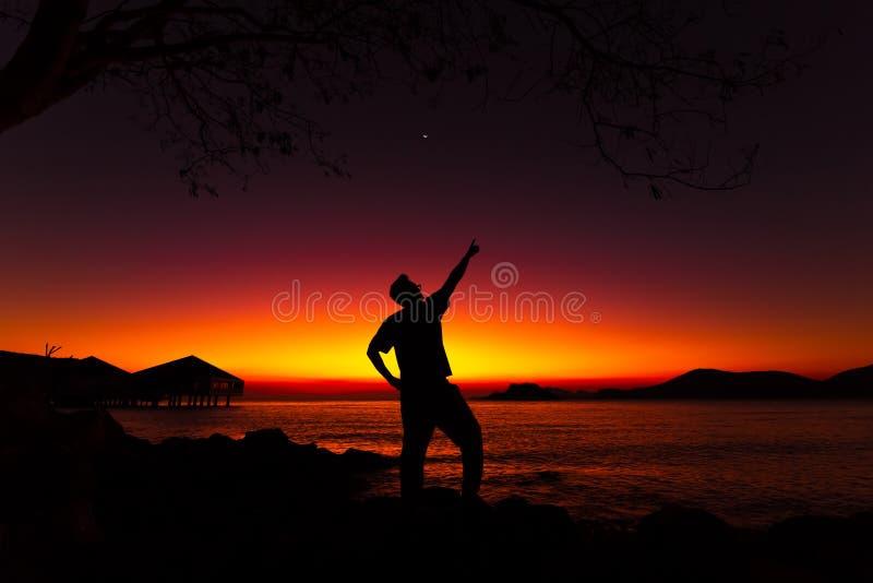 Сильуэт, человек, указывающий в небе на закат Фон пляжа для путешествий стоковое фото