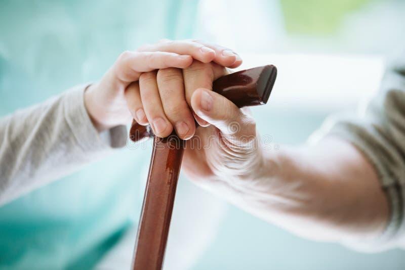 Символическое фото с руками - молодой помогая старейшина одно стоковые изображения rf