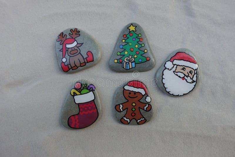 Символы рождества покрашенные на камнях над белым песком стоковое фото