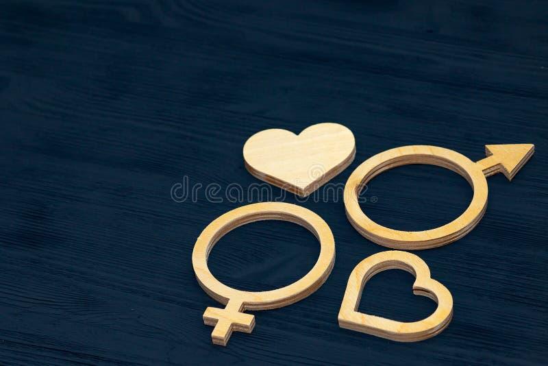 Символ равенства полов сделанный из переклейки Черная деревянная предпосылка Мужчина и женские символы стоковое фото
