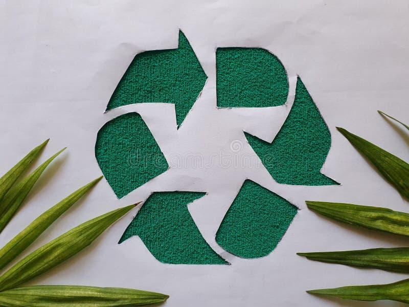 символ рециркуляции в зеленом, пальмовом листьях и белом фоне стоковое фото