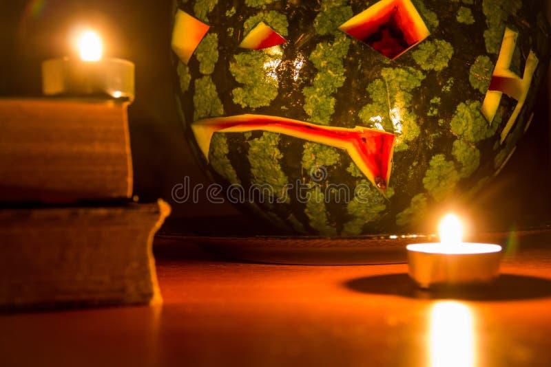 Символ хеллоуина, арбуз с высекаенной красной усмехаясь стороной и горящие свечи на темной предпосылке стоковые фото