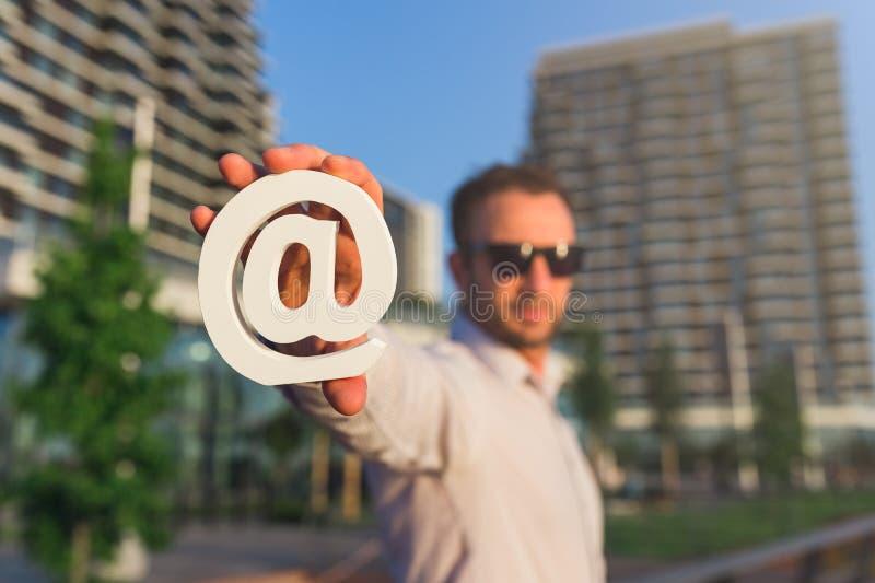 Символ электронной почты удерживания бизнесмена перед организациями бизнеса Свяжитесь мы концепция стоковая фотография rf