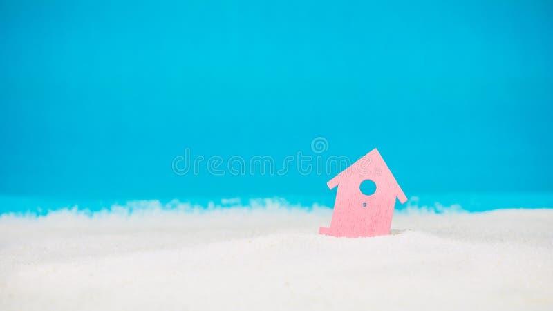 Символ меньшего красного дома на песке с яркой голубой предпосылкой стоковая фотография rf