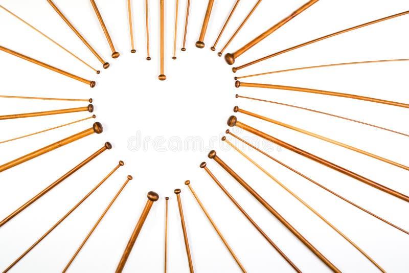 Символ сердца сделанный деревянных вязать игл на белой предпосылке стоковое фото