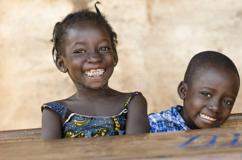 Символ счастья: Пары африканских детей смеясь над на школе стоковые изображения