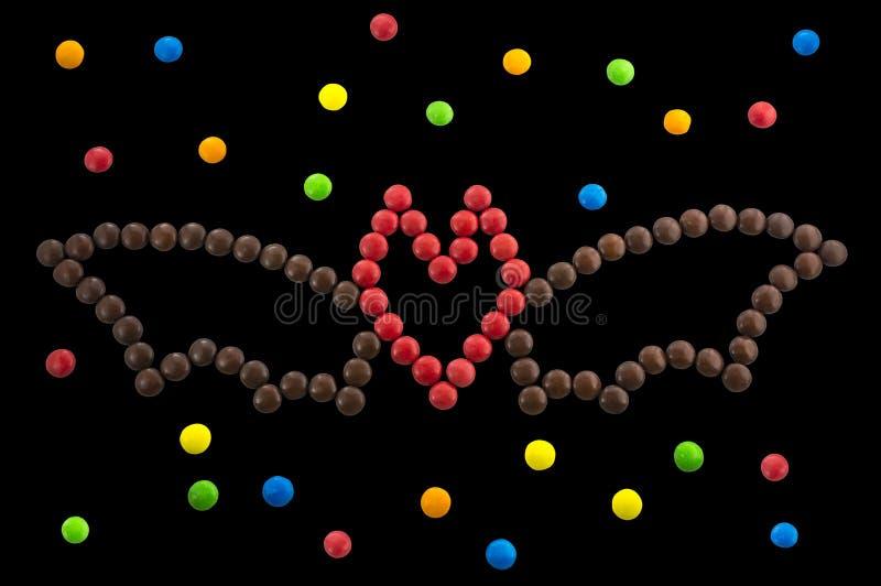 Символ хеллоуин - летучая мышь из круглых изолированных конфет стоковое изображение