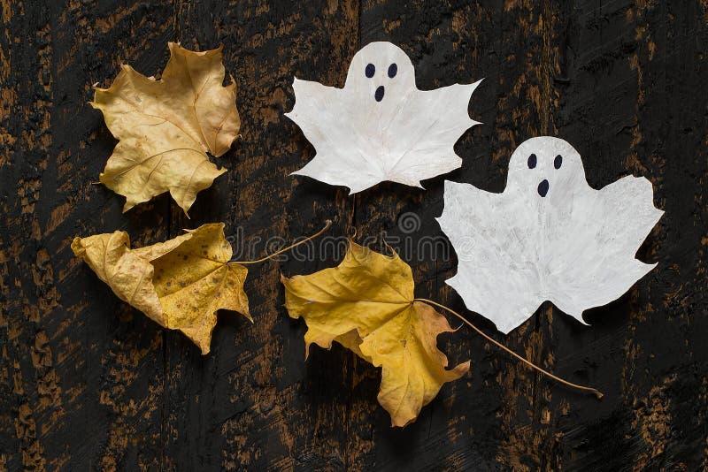 Символ хеллоуин - призрак и кленовые листы стоковые изображения
