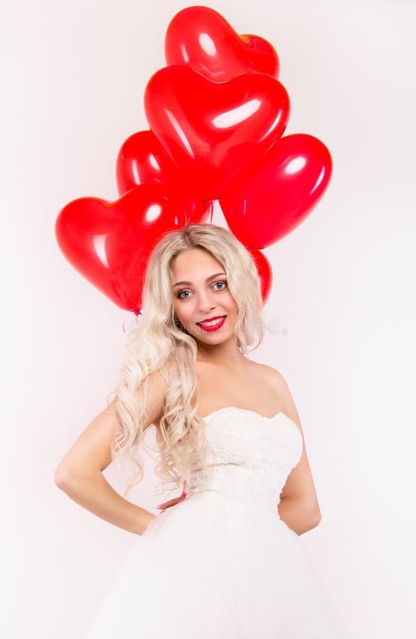 Симпатичная девушка в белом платье с красными воздушными шарами Романтичная принципиальная схема стоковое изображение rf