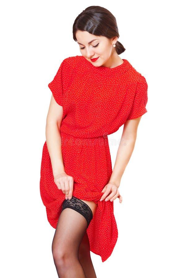 Симпатичная девушка в красном платье выправляет чулки стоковое фото rf