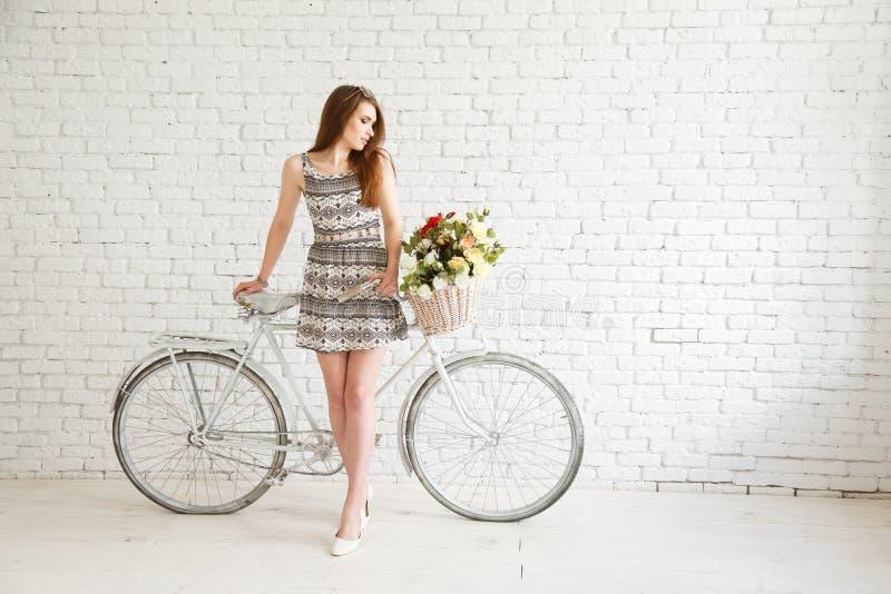 Симпатичная девушка с велосипедом и корзиной цветков на предпосылке белой кирпичной стены стоковые изображения