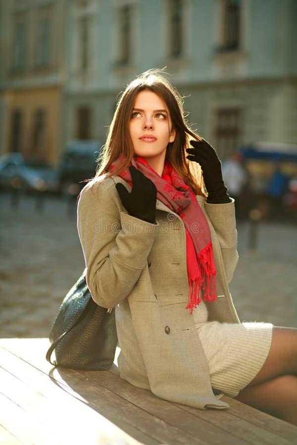 Симпатичная женщина в пальто сидя на улице города в солнечном свете стоковые фотографии rf