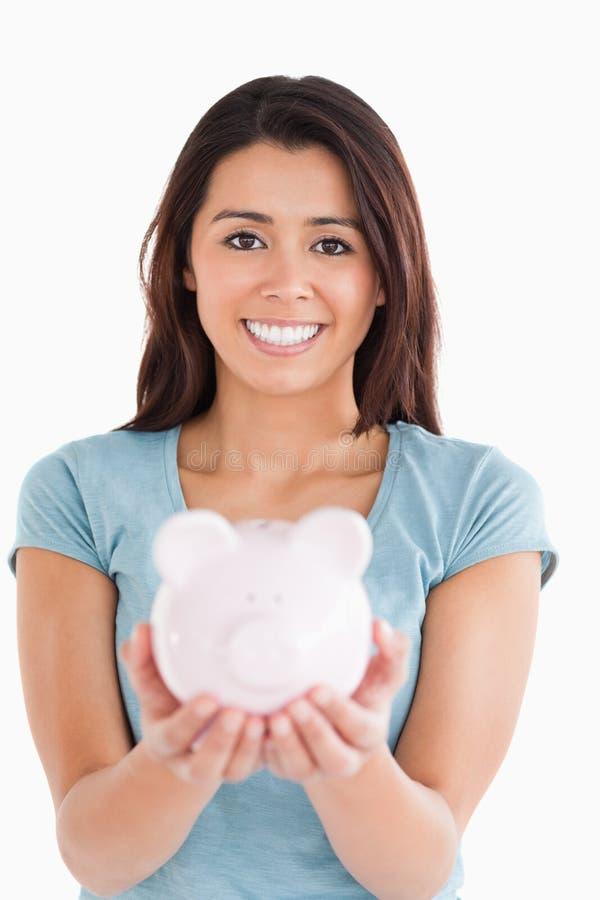 Симпатичная женщина представляя с piggy банком стоковое изображение rf