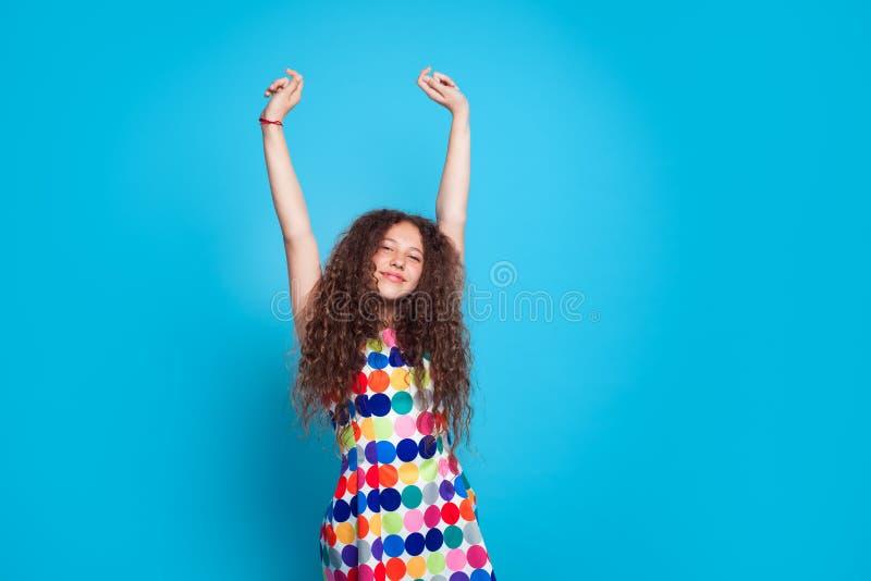 Симпатичная женщина протягивая вверх на сини стоковые фото