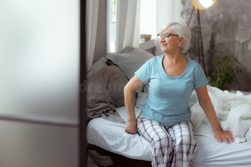Симпатичная женщина смотря в окна пока сидящ на кровати стоковая фотография rf