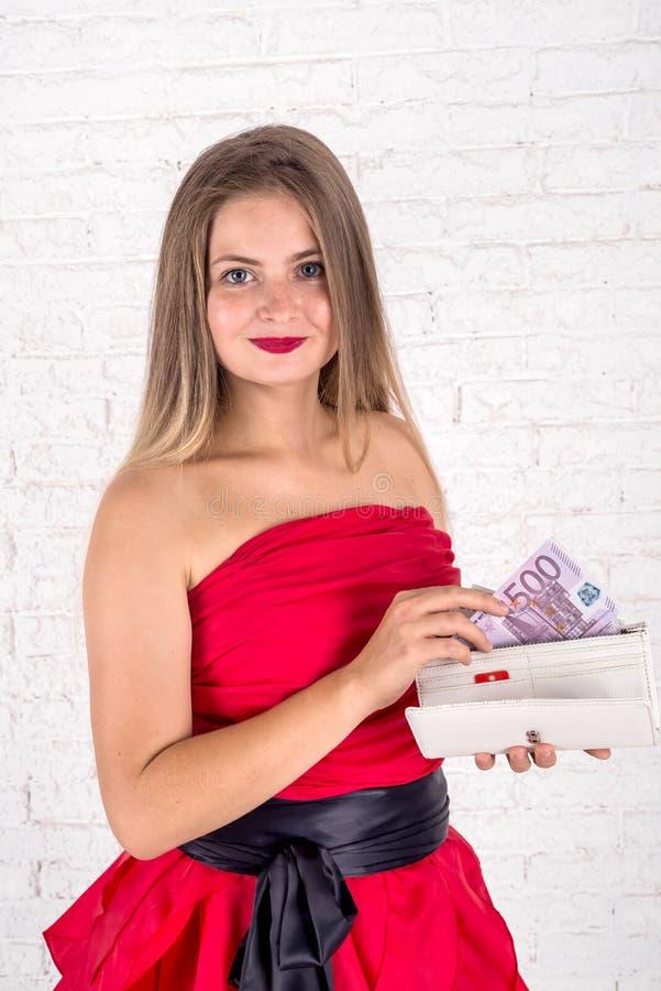 Симпатичная женщина с счетами портмона и евро стоковое фото rf