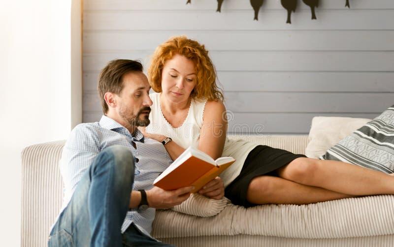 Симпатичная книга чтения пар совместно дома стоковая фотография rf