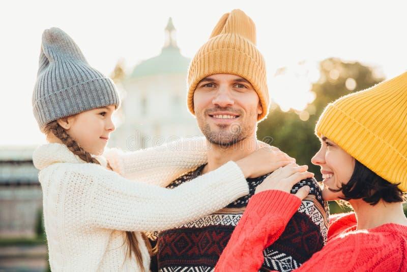 Симпатичная малая девушка наслаждается временем с родителями, обнимает ее отца с большой влюбленностью, проводит выходные осени с стоковые изображения