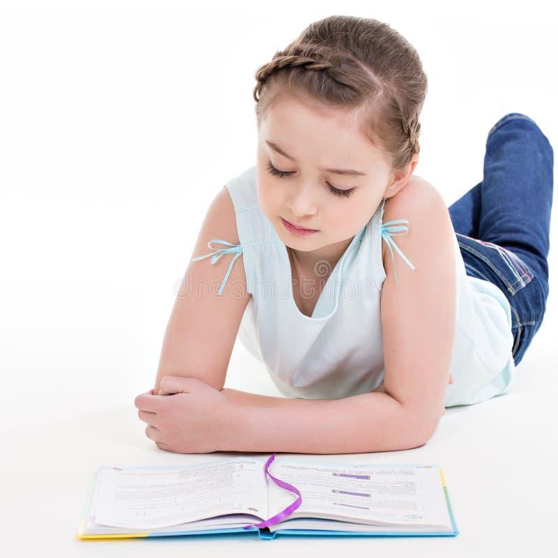 Симпатичная маленькая девочка лежит с книгой стоковые фотографии rf