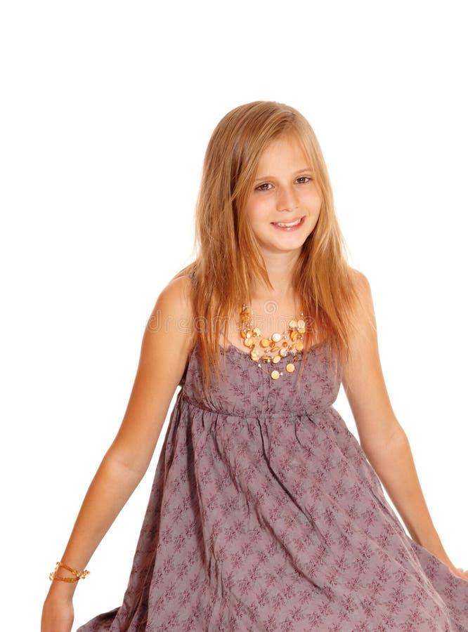 Симпатичная маленькая девочка сидя на поле стоковые фото