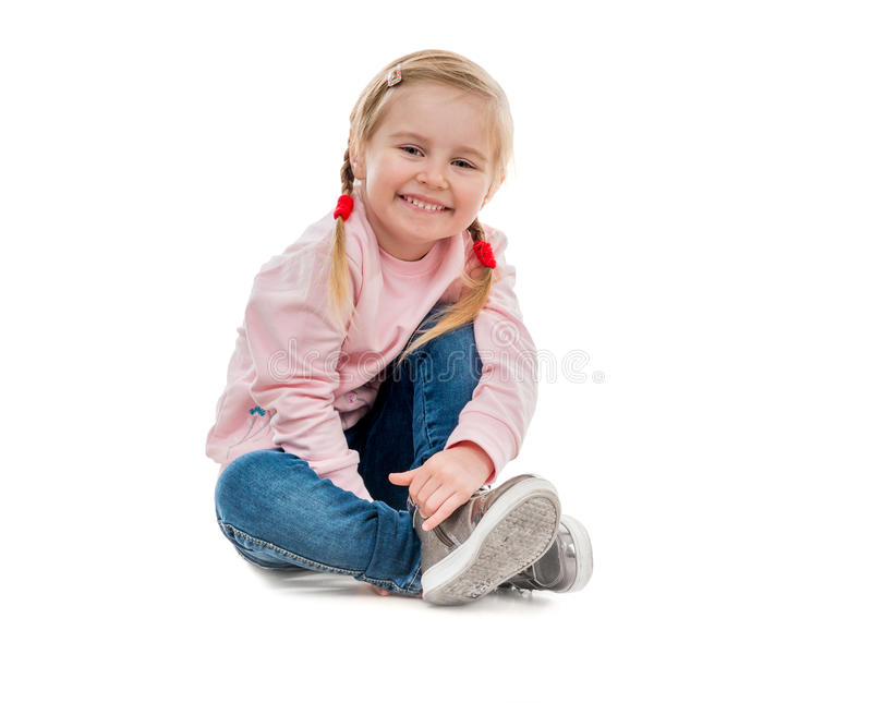 Симпатичная маленькая девочка сидя на поле стоковое фото rf