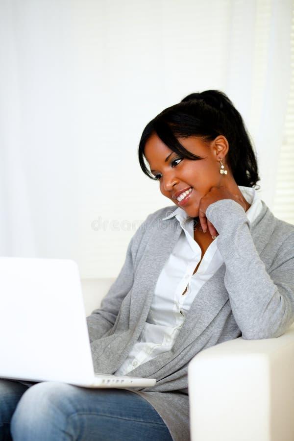 Симпатичная молодая женщина ся и смотря к компьтер-книжке стоковая фотография rf