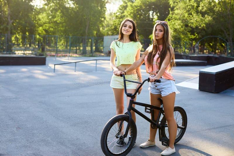 Симпатичная молодая женщина с велосипедом на предпосылке города в солнечном свете внешнем Активные люди 2 милых девушки с bmx стоковое фото rf
