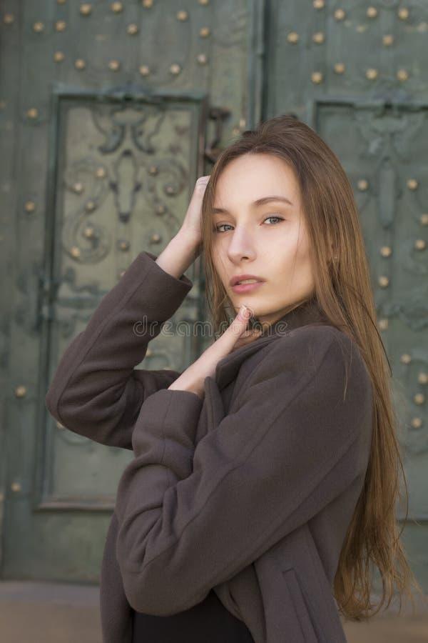 Симпатичная молодая белокурая женщина в сером пальто стоковое изображение rf