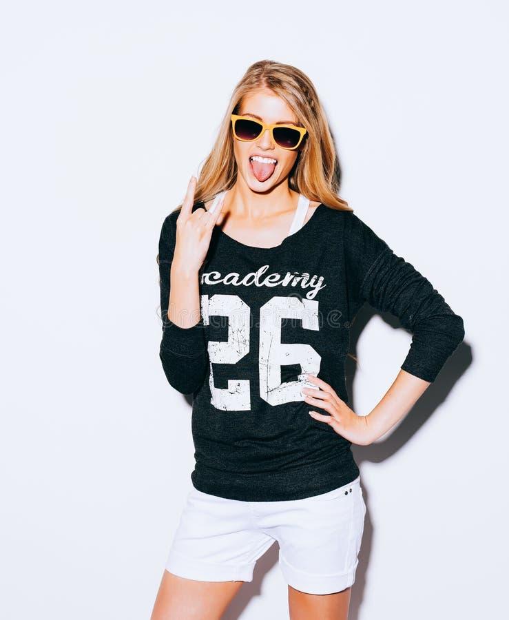 Симпатичная молодая белокурая женщина делая звонком меня жест и показывая язык в suglasses, фуфайке и белых шортах Белая предпосы стоковые фотографии rf