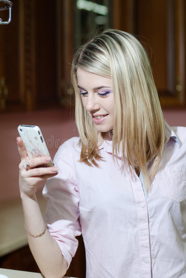 Симпатичная молодая женщина используя мобильный телефон стоковое изображение