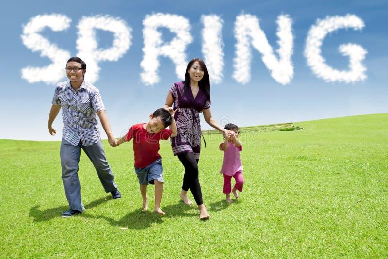 Симпатичная молодая семья бежать на луге стоковое изображение