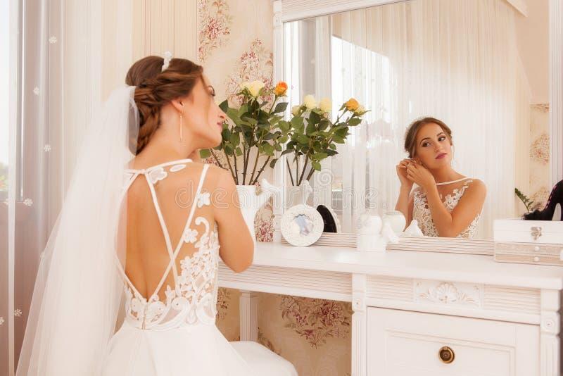 Симпатичная невеста, модель подготавливая к дню свадьбы перед зеркалом стоковое фото rf