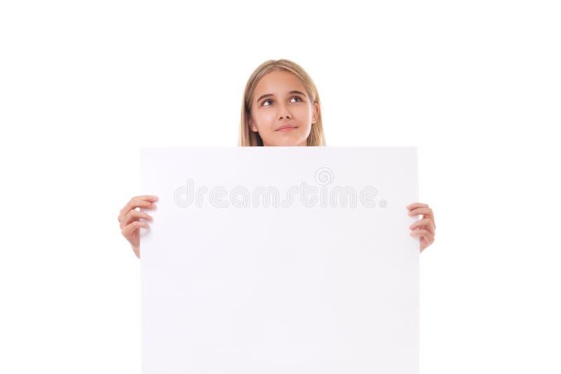 Симпатичная предназначенная для подростков девушка смотря вверх за пустой изолированной доской, стоковое изображение