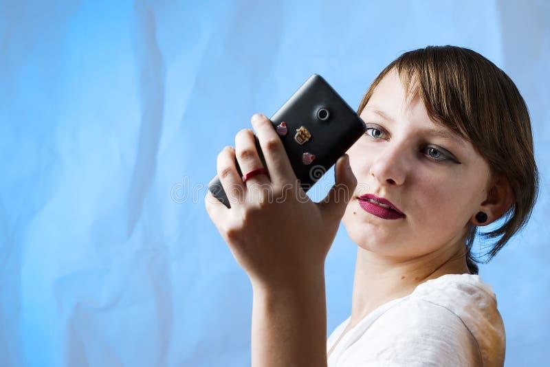 Симпатичная славная макетированная девушка с телефоном стоковое фото