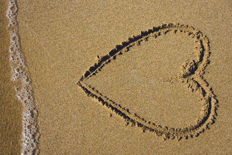 Симпатичное сердце в песке с океаном и море пенятся на пляже стоковые изображения rf