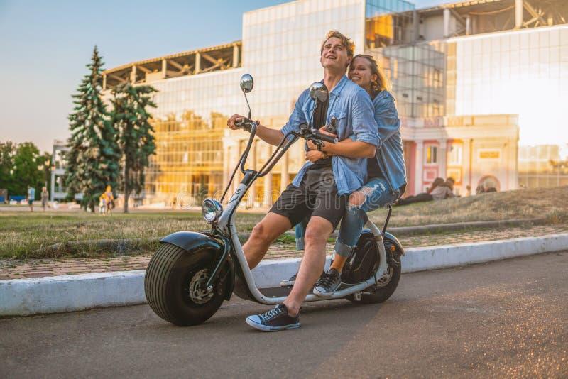 Симпатичные молодые пары управляя электрическим велосипедом во время лета стоковая фотография