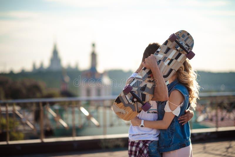 Симпатичные пары активных скейтбордистов обнимают и целуют запальчиво, прячут за скейтбордом, стойкой против стоковые фото