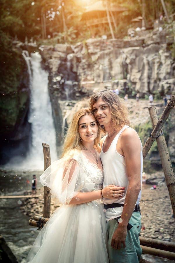 Симпатичные пары свадьбы против водопада на заходе солнца, тропического острова Бали стоковая фотография