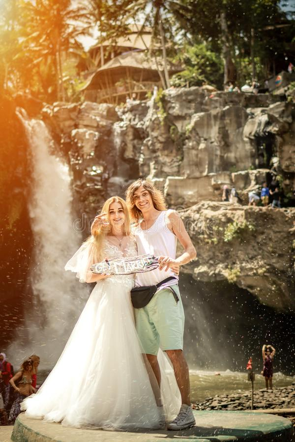 Симпатичные пары свадьбы против водопада на заходе солнца, тропического острова Бали стоковое фото