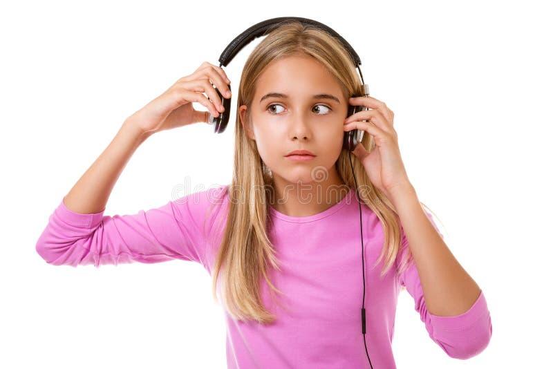 Симпатичный девочка-подросток извлекая ее изолированные наушники для шума или громкой музыки, стоковая фотография rf