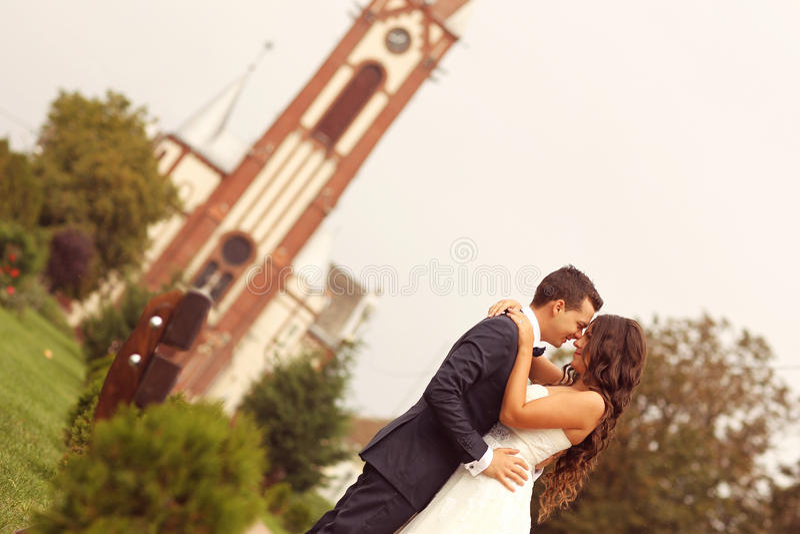 Симпатичный жених и невеста перед церковью стоковые фото