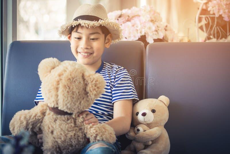 Симпатичный момент азиатского милого мальчика играя с куклой стоковая фотография